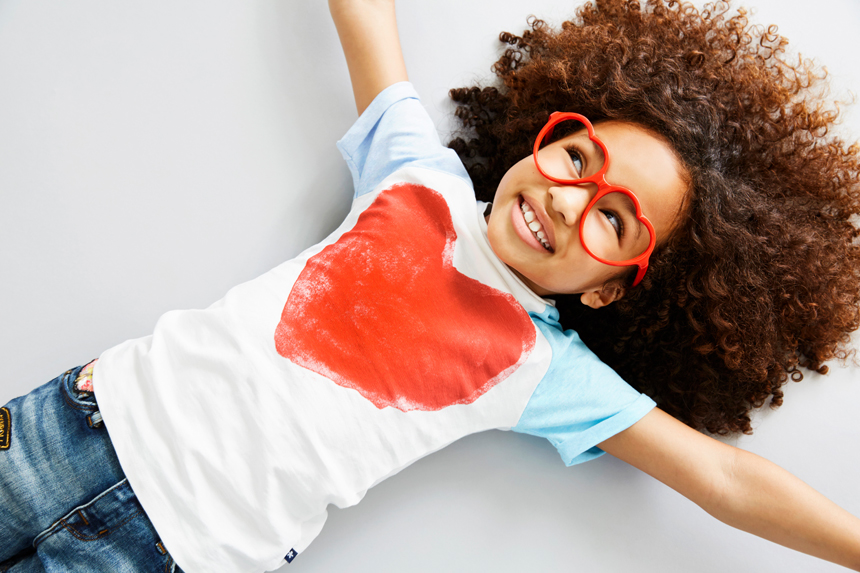 Happy multiracial girl with natural hair and red glasses for Zappos.